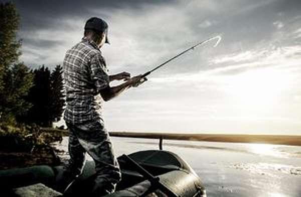 Рыбак рыбачит с лодки